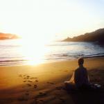 woman sitting on beach at sunset
