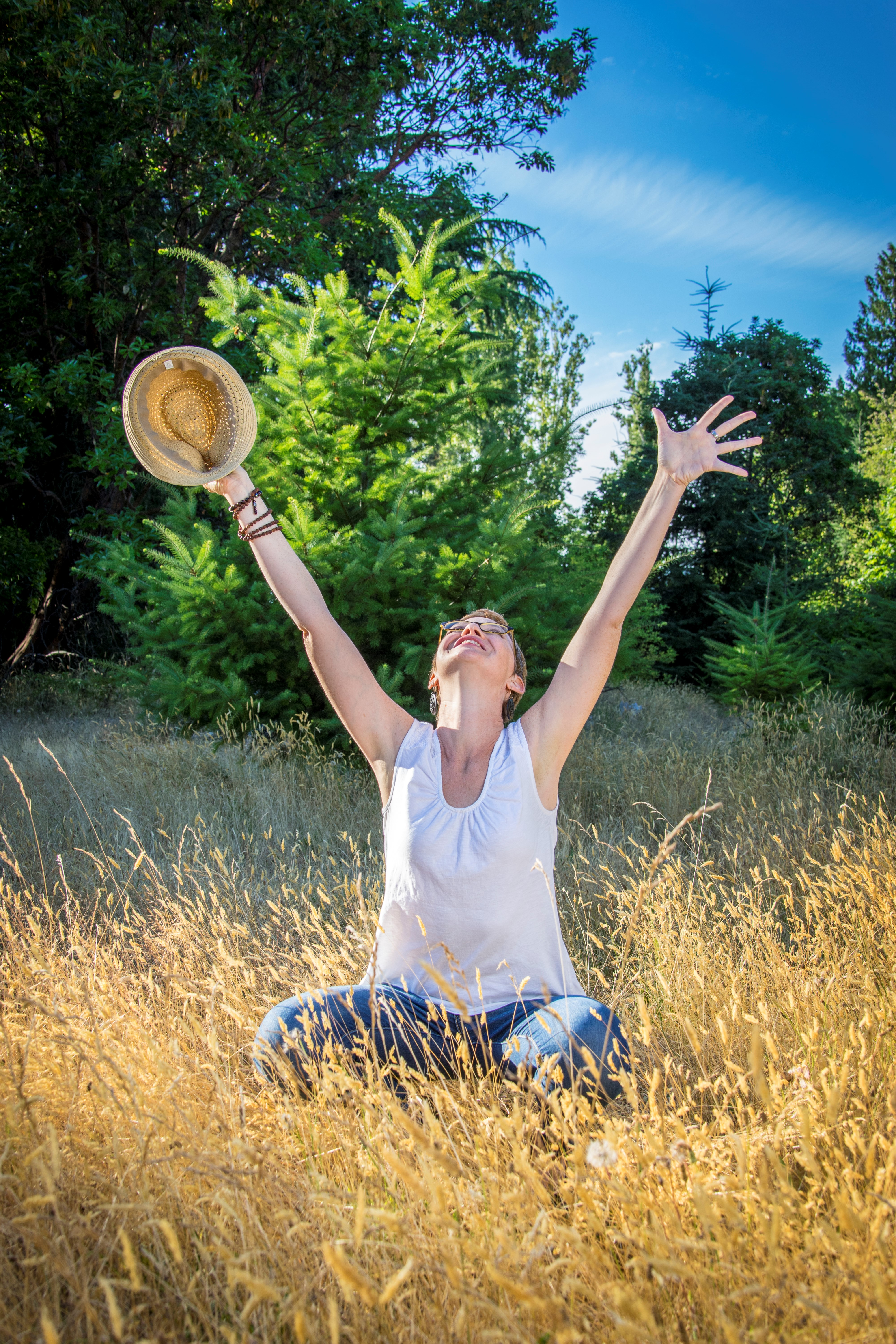 woman sitting in tall grass arms up with a hat in her hand