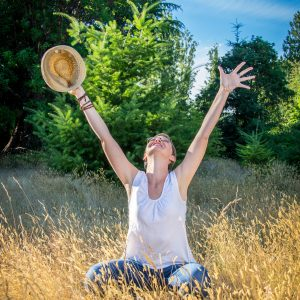 woman sitting in tall grass looking up with arms up smiling