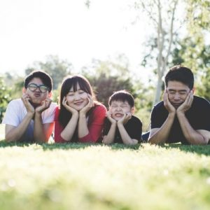 asian family laying in the grass making funny faces